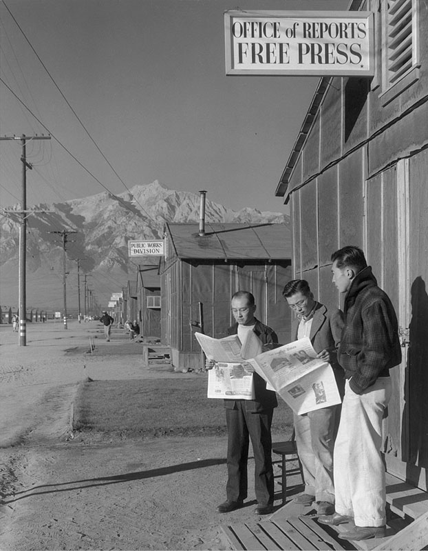 Roy Takeno (far left), with Yuichi Hirata and Nabou Samamura, read the Los Angeles Times in the Manzanar Relocation Camp in California in 1943. Photograph by Ansel Adams.